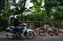 Motorcyclists driving by a heap of trash on the side of the road